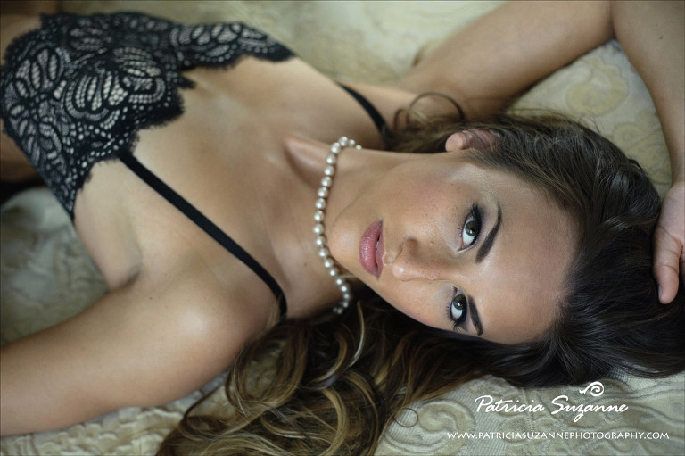 Boudoir photograph of woman on bed with pearls and lace bustier