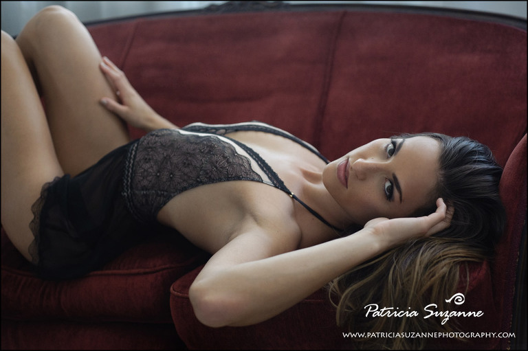 boudoir photograph of woman in black teddy on red antique sofa