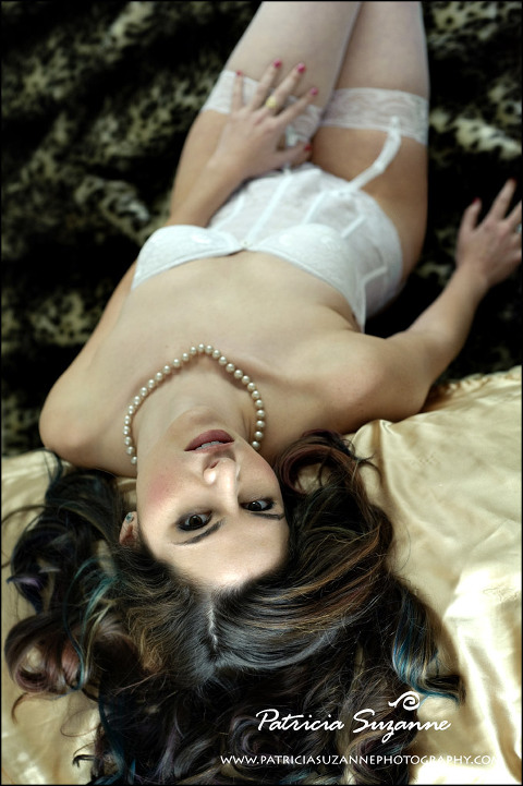 dark haired woman in white lace lingerie on satin sheets